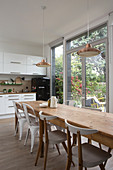 Long wooden table and chairs next to balcony doors in white, open-plan kitchen
