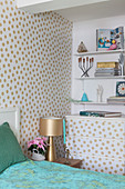 Polka-dot wallpaper on wall and chest of drawers in bedroom