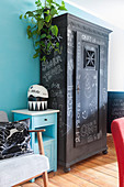 Old cupboard painted with chalkboard paint and covered in chalk lettering