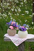 Spring flowers in spherical vases in garden