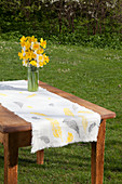 Vase of narcissus on table runner printed with pattern of feathers in garden