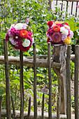 DIY-Rosenkugel aus Dahlien, Phlox und Stockrosen am Gartenzaun
