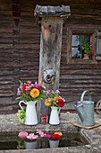 Sträusschen aus Pompondahlien, Salbei, Phlox und Löwenmäulchen in weißen Milchkannen auf Brunnenrand