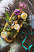 Kerzen in Eiform und bepflanzte Eierschalen im Eierkarton