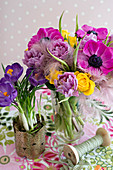 Lavish bouquet in glass vase and crocuses planted in pot
