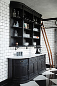 Schwarz gestrichene Anrichte aus ehemaligem Bücherregal an gefliester Wand in schwarze-weißer Küche