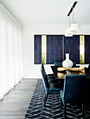 Black dining table with blue chairs, blue carpet and blue and brass artwork