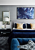 Double bed in the bedroom with blue accessories and wallpaper with metal mesh