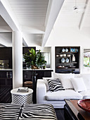 Open living room with white upholstered sofa, pillows and ottoman in zebra look