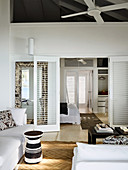 Living room with white upholstered furniture and black and white side table, view through open double doors into the bedroom