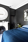 Double bed with dark blue bedspread, fireplace and mirror in the bedroom with black walls