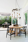 Designer table with chairs, pendant lamp above with leaf garland in the dining room