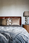Gray fur blanket on the bed with various pillows