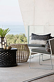 Delicate coffee tables and armchairs on balcony with sea view