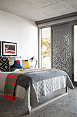 Verschiedene Farben und Muster auf dem Bett im grauen Schlafzimmer