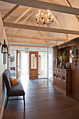 Couch against half-height partition and antique dresser in converted stable with exposed wooden roof structure
