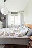 Ungemachtes Doppelbett mit Holzkopfteil, Glühfadenlampe auf dem Nachttisch