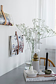 Glass vase and candlestick on grey dining table next to leather magazine holders on wall