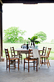 Wooden chairs around table on concrete floor with view of green garden