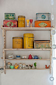 Brightly coloured tins and doll's crockery on old wall-mounted shelves