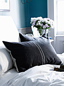 Two anthracite pillows with pale grey strips on white bedlinen