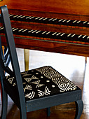 Old chair with black and white fabric seat cushion at old keyboard instrument