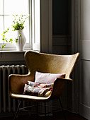 Colourful patchwork cushions on retro armchair below window