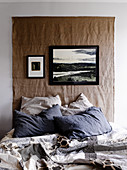Wall-hanging made from coarse fabric above bed with patchwork quilt