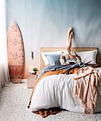 Schlafzimmer in Pastelltönen, Junge Frau auf Doppelbett, daneben Pendelleuchte und Surfbrett