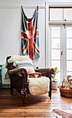 Vintage animal hide leather armchair in front of Union Jack flag on wall