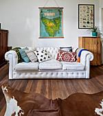 Vintage Ledersofa in Weiß mit Kissen und Tierfellteppich im Wohnzimmer