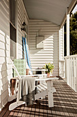 Deck chair on veranda with white painted wooden paneling