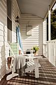 Liegestuhl auf Veranda mit weiß gestrichener Holzverkleidung