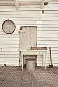 Drawer table on veranda with white painted wood paneling