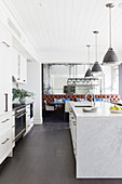 Kitchenette and marble kitchen island under pedal lights in an open living room