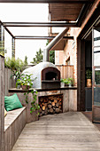 Pizza oven with firewood on wooden terrace