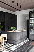 Concrete kitchen island in front of black built-in kitchen
