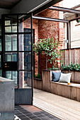 Built-in bench and plants on terrace with brick wall and industrial door