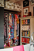 Colourful patterned dresses in open-fronted wardrobe and shelves of books sorted by colour