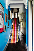 Brightly striped carpet on staircase with bright blue wall