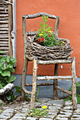 Wreath woven from vine tendrils on rustic chair made from rough branches
