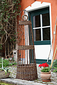 Decorative wicker obelisk outside house