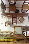 Alte Stühle an der Wand einer Korbflechterei