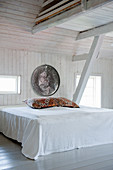 Bed in attic bedroom with white wooden walls and exposed roof beams