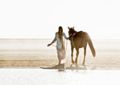 Woman and horse walking side-by-side on beach