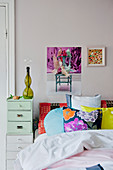 Patterned scatter cushions on bed with chest of drawers as bedside table