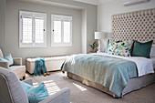 Schlafzimmer in Naturtönen, Doppelbett mit hohem, gepolstertem Betthaupt