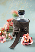 Fabric roses and bottle tied with leather bow on grey surface
