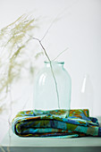 Twig in glass jar on blue and green folded cloth