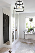 Silver console table below window and wardrobe with mirrored doors in bedroom